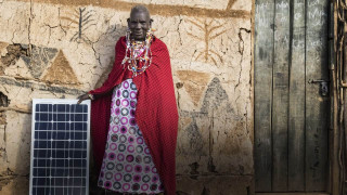 African traibal person standing next to solar panel